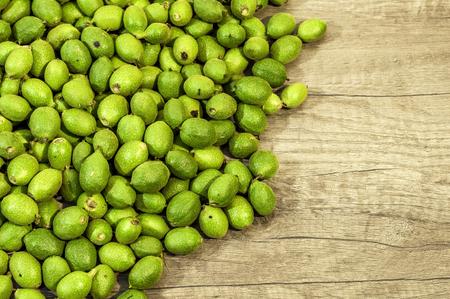 Muchas nueces jóvenes verdes en cáscaras de mesa de madera Foto de archivo