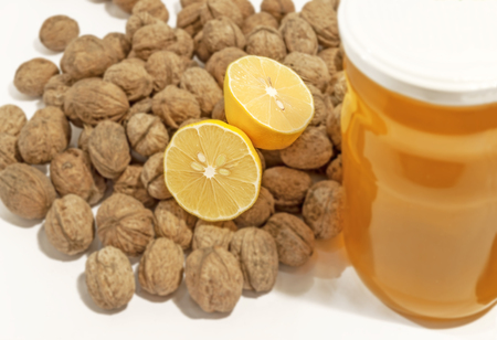 Jar of honey with lemon and walnuts on white