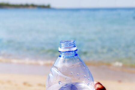 Pet bottle with water on the sea sand