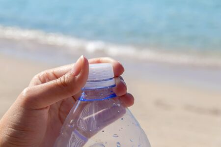 Pet bottle with water on the sea with hand closing plug