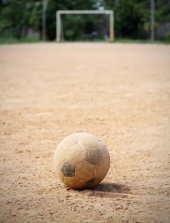 lejos: Un balón de fútbol viejo en el suelo, el objetivo es el fondo Foto de archivo