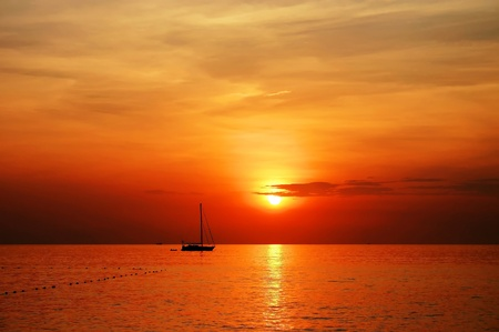 red sunset: sailing boat sunset at kata beach phuket  Stock Photo