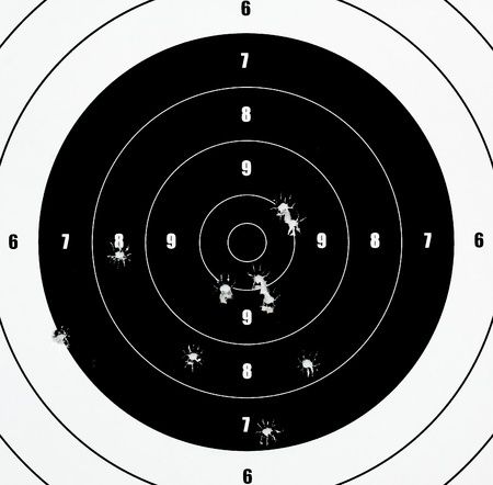 A Closeup of a practice target used for shooting with bullet holes in it. photo