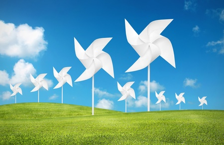 traditional windmill: paper toy windmill in green grass field Stock Photo