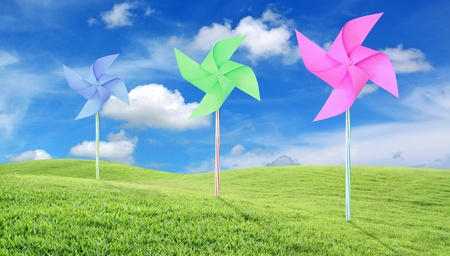 colorful paper toy windmill in green grass field  photo