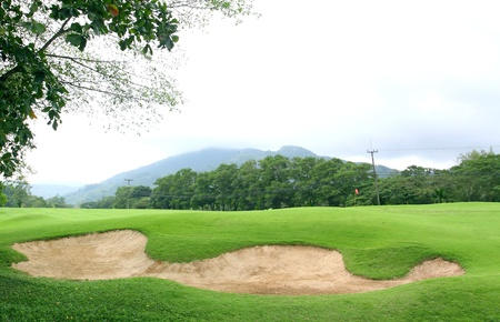 Sand bunker on the golf course with green grass and trees photo