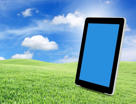 tablet pc on green grass photo