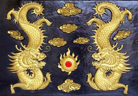 dos de oro dragones (en chino: Largo) tallado en madera en el fondo negro.