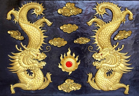 wood carvings: two golden dragons (Chinese: Long) wood carving in black background. Stock Photo