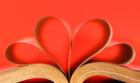 Heart-shaped book on red background photo