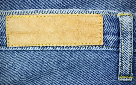 Blank leather jeans label sewed on a blue jeans, used as background for your text.  photo