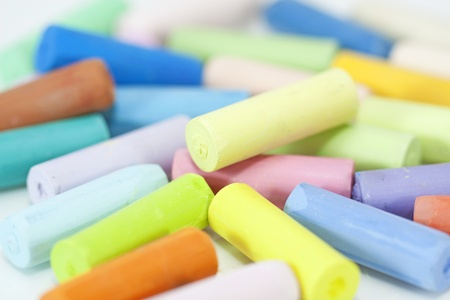 art and craft equipment: chalks in a variety of colors on a white background  Stock Photo