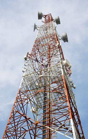 Red and white tower of communications with their telecommunications antennas  photo