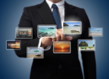 hombre empujando: Hombre de negocios empujando la pantalla virtual con diferentes im�genes del mar tropical, Islas Andaman