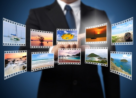 Businessman pushing many image in film button on the whiteboard   photo
