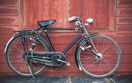 Vintage Bicycle standing near a vintage wood wall photo