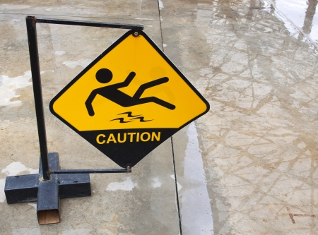 Yellow sign alerts for wet floor   photo