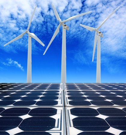 Solar panels and Wind Turbines under cloudy blue sky