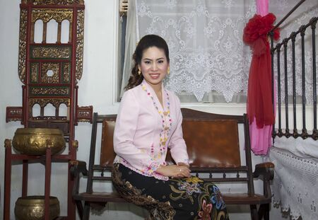 portrait of beautiful asian woman smiling with traditional clothing Peranakan dress photo