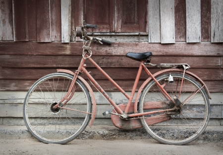 Old bicycle leaning against grungy barn  Stock Photo