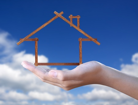 wood  house in hand on blue sky  photo