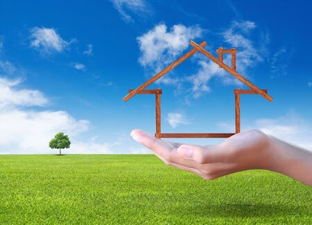 Hand showing House on the green field Stock Photo - 16991398