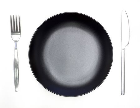 Knife, black plate and fork isolated on white background photo