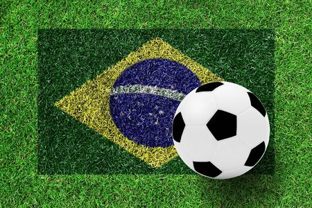 soccer ball on flag of Brazil as a painting on green grass photo