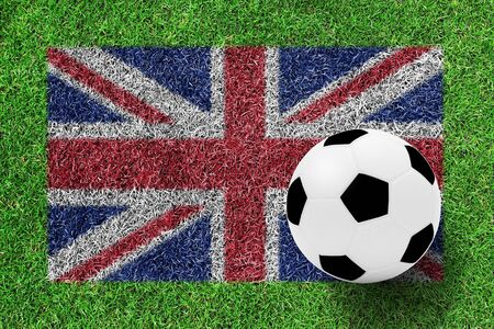 soccer ball on flag of british as painting on green grass background photo