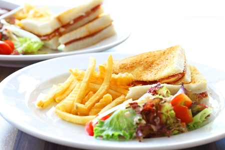 Delicious club sandwich with french fries and salad photo