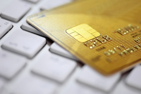 Close up of golden credit card on a computer keyboard. Concept of internet purchase  photo