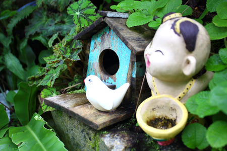 Old blue bird house with ceramic bird and boy  photo