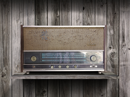 Vintage radio receiver device on old wooden shelf  photo
