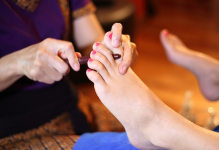 reflexology foot massage, spa foot treatment by wood stick,Thailand Stock Photo - 23447306
