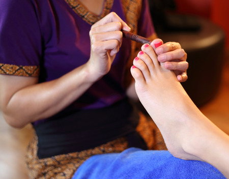 reflexology foot massage, spa foot treatment by wood stick,Thailand  photo