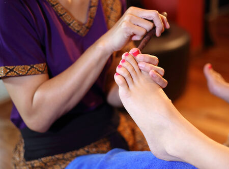 reflexology foot massage, spa foot treatment by wood stick,Thailand Stock Photo - 23447310
