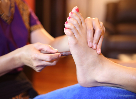 reflexology foot massage, spa foot treatment by wood stick,Thailand  Stock Photo - 23447311
