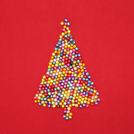 Christmas tree decorate by colorful beads on red background  Stock Photo