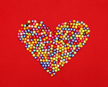 Colorful beads heart shape isolated on red background  photo