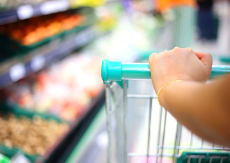 woman hand with shopping cart in supermarket photo