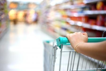 vrouw hand met een winkelwagentje in de supermarkt