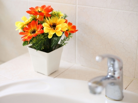 Artificial flowers at wash basin in a bathroom  photo
