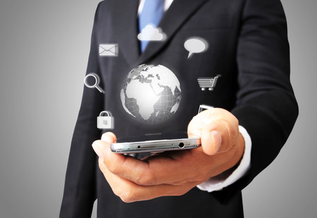 Business man hold smart phone with glowing digital wire globe  photo