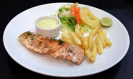 Grilled Salmon with Fresh Salad Leaf and french fries photo