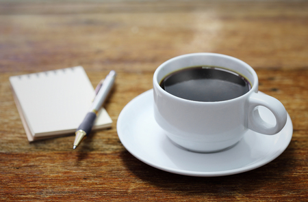 Coffee cup notebook and pen on the wooden table background  photo