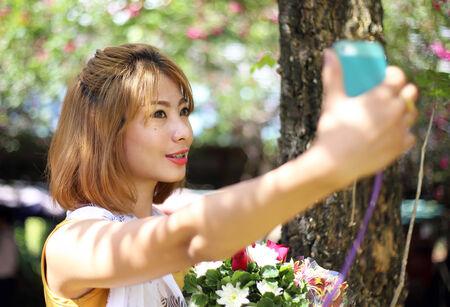 Asian girl taking selfie photo hold flower in garden photo