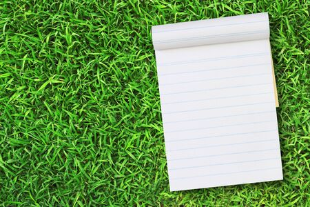 Blank notebook on Green Grass background. photo