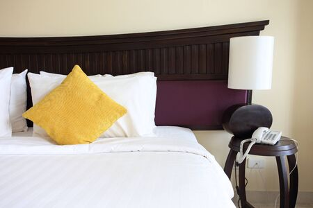 bedsheets: Bed pillows and lamp in the hotel room Stock Photo