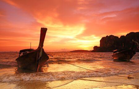 railay: longtail boat sunset at Pranang beach Railay krabi Thailand