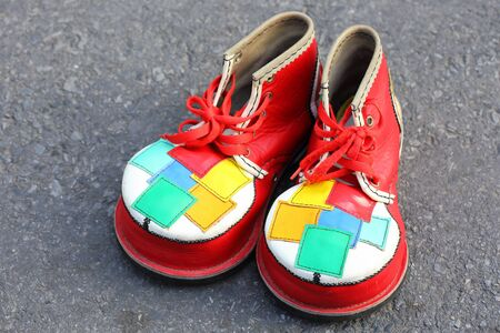 A pair of colorful clown shoes on the walk way floor photo